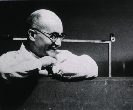 <p>Head and shoulders, right pose, leaning on enclosure; watching laboratory experiment; wearing glasses.</p>