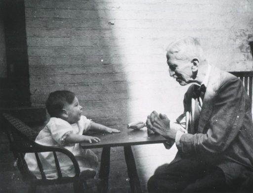 <p>Half length, seated at table with infant.</p>