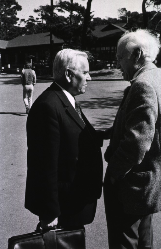 <p>Academician A.A. Bayov (left, standing, facing right), director of the U.S.S.R. Academy of Science, Institute of Molecular Biology and chief of the Soviet delegation to the Asilomar Conference, talking with another researcher at the Asilomar Conference, Pacific Grove, California, Febrary 24-27, 1975.</p>