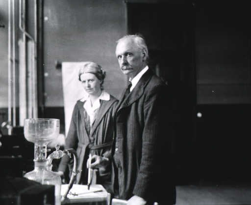 <p>Three quarters length, standing, with his assistant Miss D. Hargood-Ash, in laboratory.</p>