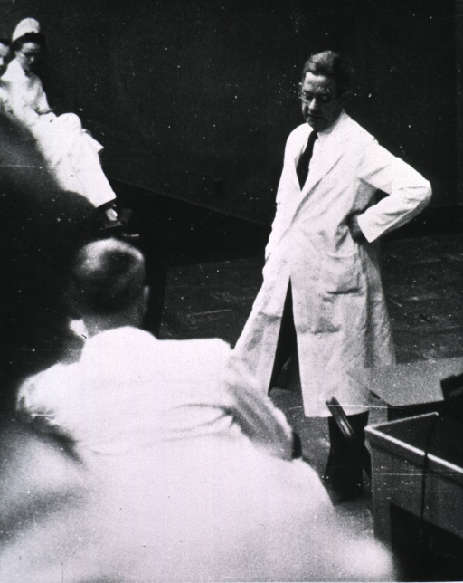 <p>Full length, turned slightly to left, wearing glasses and lab coat, standing in front of group of doctors and nurses on surgery rounds.</p>