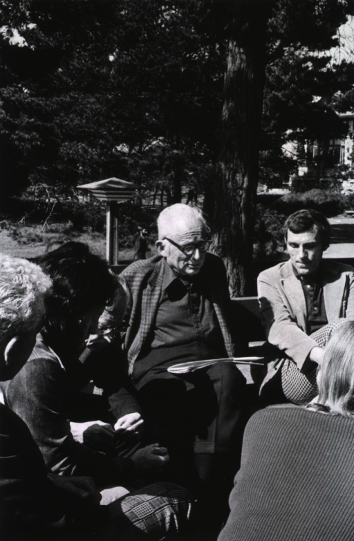 <p>Dr. DeWitt Stetten, Chairman of the RAC, (center, facing front) seated on park bench talking to other researchers circled around him at the Asilomar Conference, Pacific Grove, California, Febrary 24-27, 1975.</p>