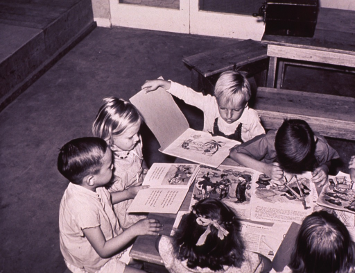 <p>Several children, sitting together at a table, are reading.</p>