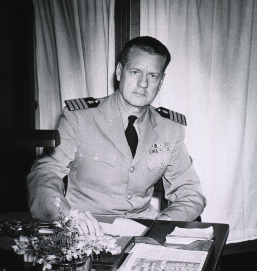 <p>Half-length, seated at desk, full face; wearing naval uniform (Captain); hand on desk.</p>