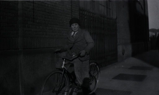 <p>View of a boy riding his bicycle on the sidewalk.</p>