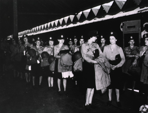 <p>A group of female military nurses in uniform stands in rows at an unidentified location.  Each nurse carries the same garment bag and helmet.</p>