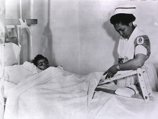 <p>African American cadet Nurse adjusting traction.</p>