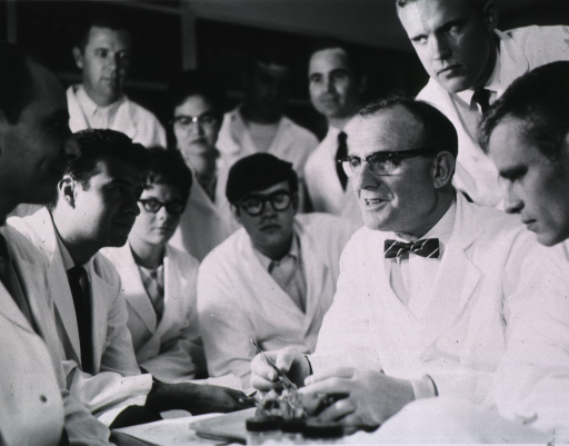 <p>Half-length, turned to left, wearing glasses and lab coat, demonstrating on a preserved heart to a group of students.</p>