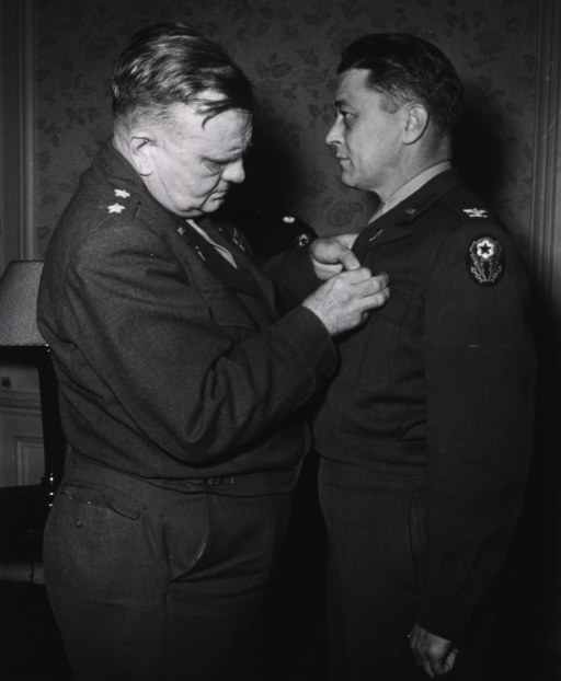 <p>The two servicemen stand in profile in a room.  Major General Hawley pins the medal on the jacket of Colonel Pillsbury.</p>