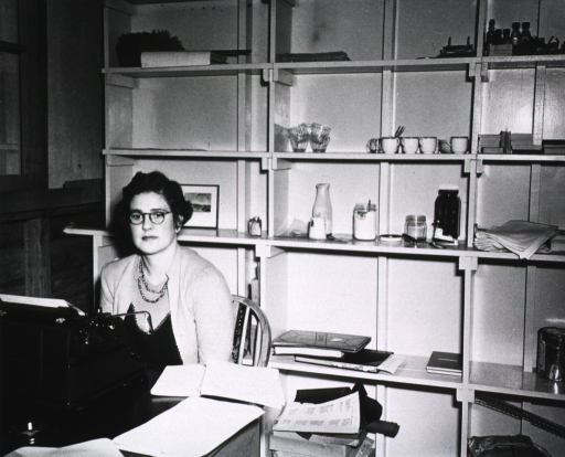 <p>A woman in civilian attire sits in front of a typewriter that is on a desk.  Behind her, on shelves, are various pharmaceutical preparations.</p>