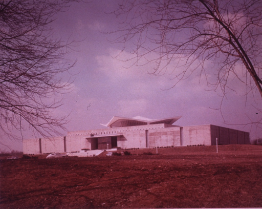 <p>Exterior view of the hyperbolic paraboloid form: front and north side of building before sod was laid; cars are in the parking lot; leafless tress are in the foreground.</p>