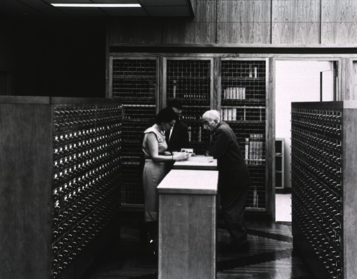 <p>Interior view: Three people are standing in front of a grated-front bookshelf and between two card catalogs.</p>