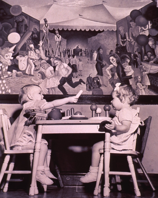 <p>Two young children are sitting at a table; circus mural is on the wall in the background.</p>