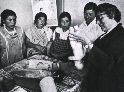 <p>Sister Ruggiero, holding a doll, instructs four pregnant women in child care.</p>