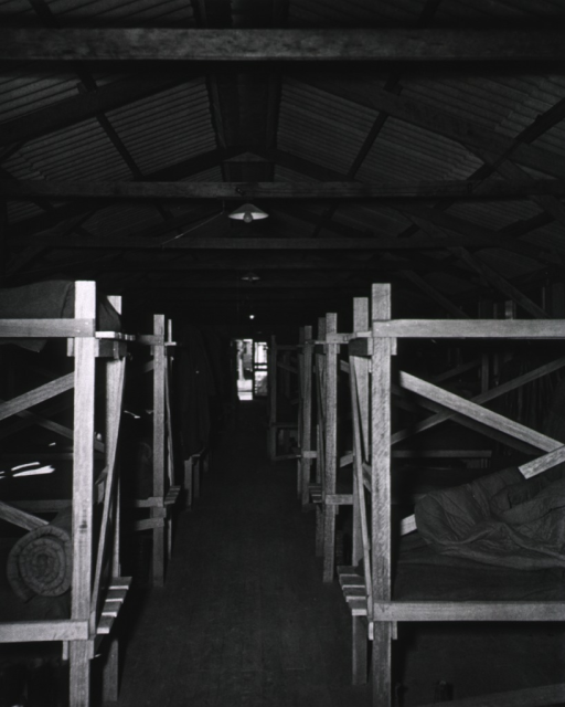 <p>On either side of a long room are rows of wooden bunk beds.</p>