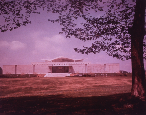 <p>Exterior view of the hyperbolic paraboloid form: front facade; car in the front of the building; tree in bloom in the foreground.</p>