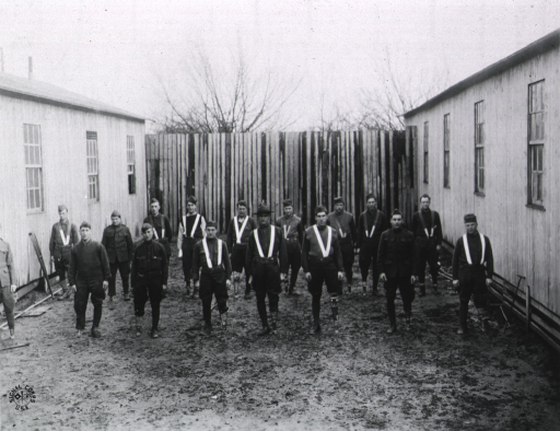 <p>A group of men with above knee amputations are standing in the courtyard between two buildings; straps over their shoulders are attached to a prosthesis which appears to be a metal frame attached to a peg.</p>