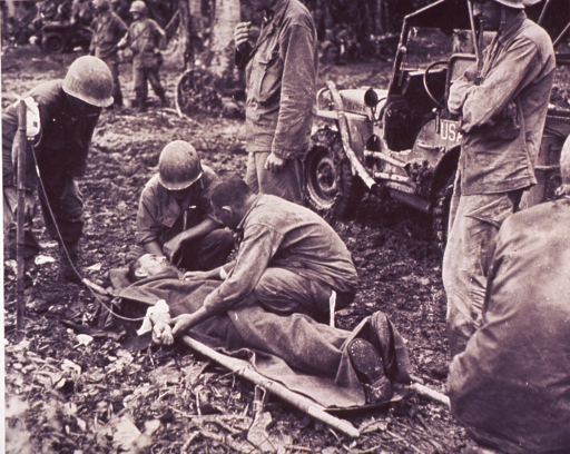 <p>A wounded soldier receives medical attention.  His is on a stretcher.  There are three men hunched over him with three others standing back and watching.  A jeep is nearby and several soldiers are in the background, near trees.  The patient has an IV line in his arm, attached to a bottle hung on a pole next to him.  According to the photo caption, this is a first aid station near Ormoc, Layte, P.I.</p>
