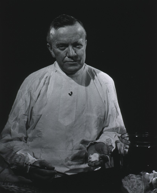 <p>Half-length, full face, wearing lab smock, seated behind counter holding mouse and pencil.</p>