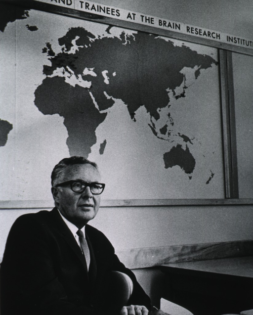 <p>Half-length, turned slightly to the right, wearing glasses, seated in front of world map at Brain Research Institute.</p>