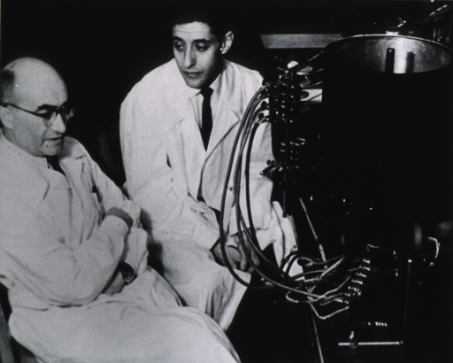 <p>Three-quarter length, seated, right pose, with Dr. Mortimer Mishkin; in front of automatic recording apparatus.</p>
