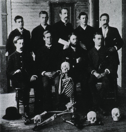 <p>Group photo:  full length, full face; others unidentified; skeleton and skulls in foreground.</p>