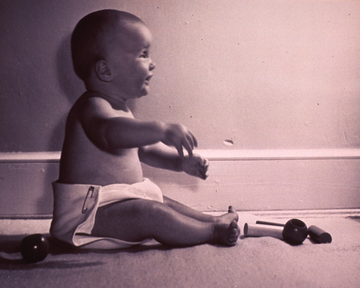 <p>Female infant, facing right, sitting up on the floor; she is wearing a cloth diaper, and there are wooden toys at her feet.</p>