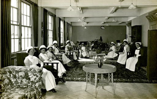 <p>Black and white photograph of the nurses' home sitting room, where 9 nurses are sitting in chairs, at King George Military Hospital, London, England.</p>