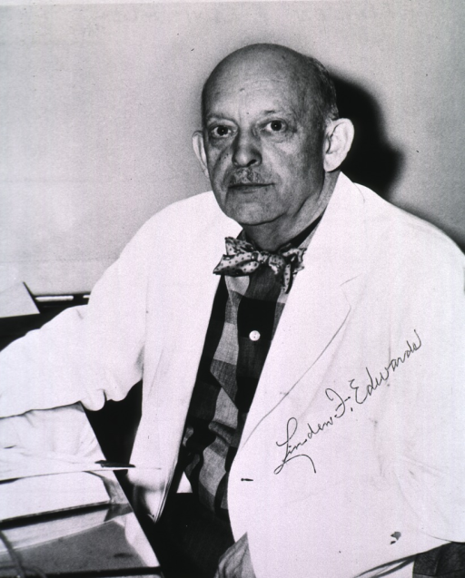 <p>Half-length, full face, seated at desk, wearing white coat.</p>