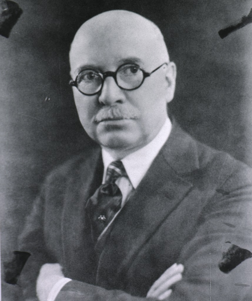 <p>Head and shoulders, left pose, full face; wearing glasses; arms folded.</p>