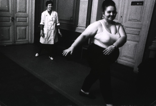<p>Interior view: an overweight woman is exercising under the supervision of a therapist standing to the left.</p>