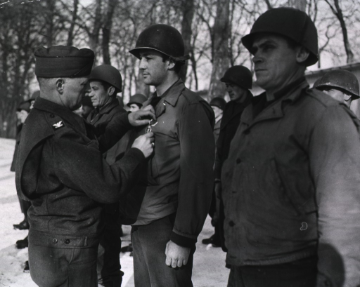 <p>Servicemen stand in rows at attention outdoors.  Snow covers the ground.  Colonel Wilson pins the cluster onto the medal of Sgt. Driscoll.</p>