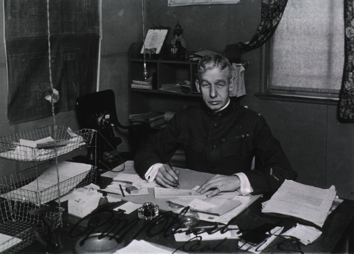<p>Seated at desk in uniform.</p>