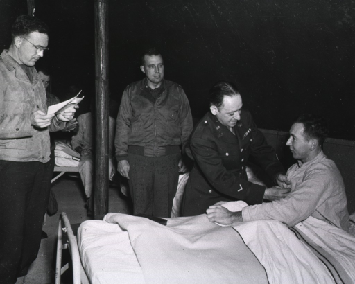 <p>Pvt. Webb sits on a bed as Mr. Cohn pins the medal on his hospital shirt.  A man stands at the foot of the bed and reads the citation.  Other servicemen sit on beds or stand in the background and watch.</p>