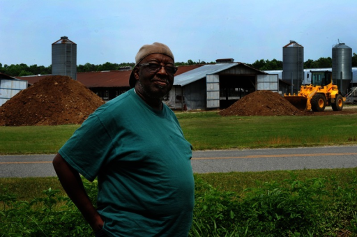 "Another Kenansville resident stands in his front yard, feet from the CAFO across the street. Donn Young, the North Carolina–based photographer who took these images, says of his time in Kenansville, ""I encountered problems with my eyes—itchy, watering, something akin to allergies."" To the people who live there, CAFOs are simply a fact of everyday life.©2013 Donn Young Photography"