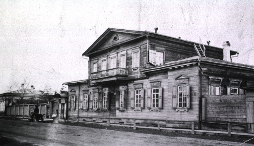 <p>Front view of the Headquarters Sanitary Department taken at an angle.  A man sitting in a wagon is in front of the building on the street.</p>