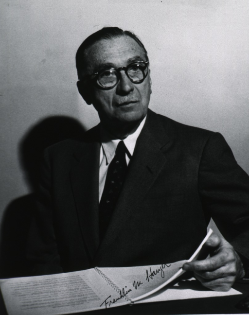 <p>Half-length, seated at desk, full face; wearing glasses.</p>