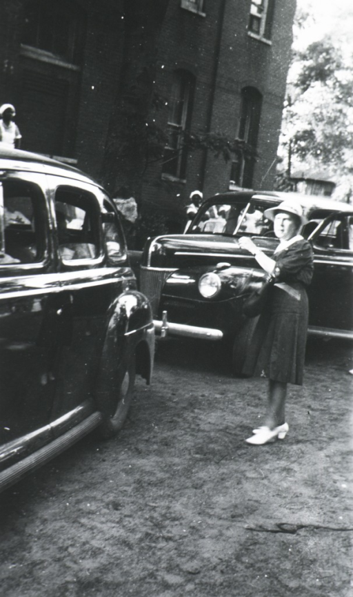 <p>Blackburn stands in the street near a car outside a building; African American nurses are behind the cars and closer to the building.</p>