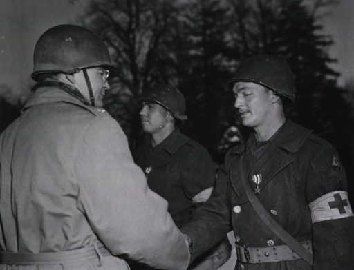 <p>Major General Oliver shakes hands with T/5 Williams.  Another serviceman stands at attention next to Williams.</p>