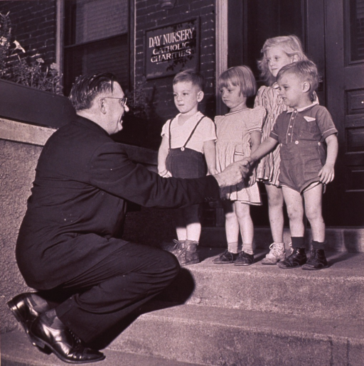 <p>Children are greeted on the steps of a Catholic Charities Day Nursery.</p>