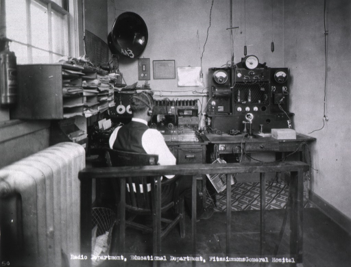 <p>Interior view of the radio department showing, from behind, a man wearing a headset and sitting at a desk on which sits the radio equipment.</p>
