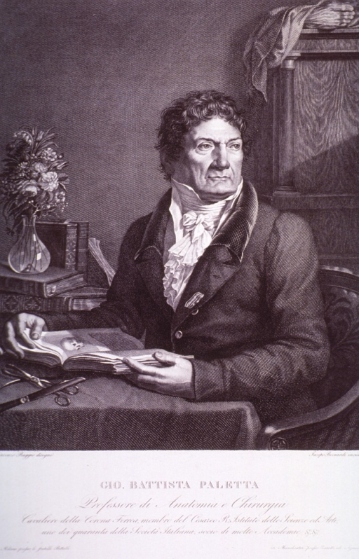 <p>Seated at table, head to right, medical book in hand, wearing decoration.</p>