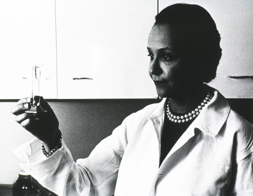 <p>Half length, three quarter face, holding chemical container in her right hand, in lab coat.</p>
