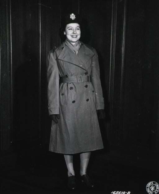 <p>A servicewoman stands in a corner and poses full-face as she models the overcoat.</p>
