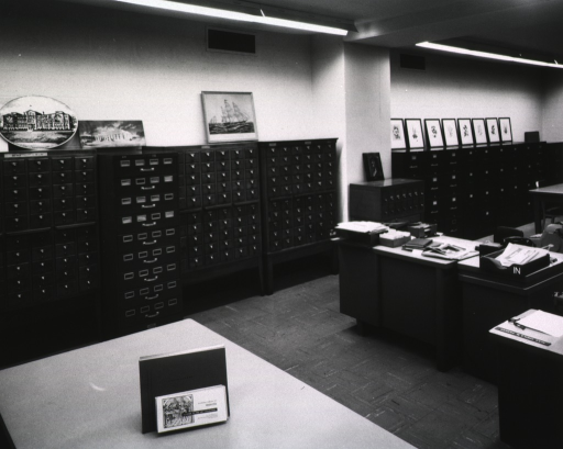 <p>Interior view: Framed and unframed pictures are on top of the file cabinets, card catalogs, and a map case that line the wall.</p>