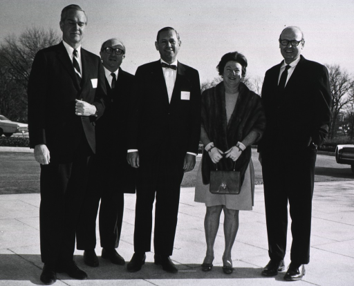 <p>Four men and a woman pose for photo on sidewalk in front of the National Library of Medicine (not shown).</p>