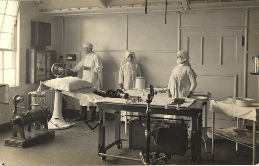 <p>Black and white photograph of 2 nurses and a doctor in the electrical treatment and x-ray room in King George Military Hospital, London, England. The room is filled with medical equipment.</p>