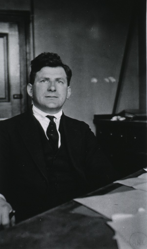 <p>Half-length, seated at desk, full face.</p>