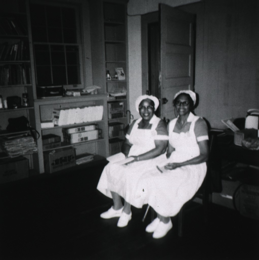 <p>View of two African American group leaders selected and trained by Miss Blackburn, sitting in a supply room(?).</p>