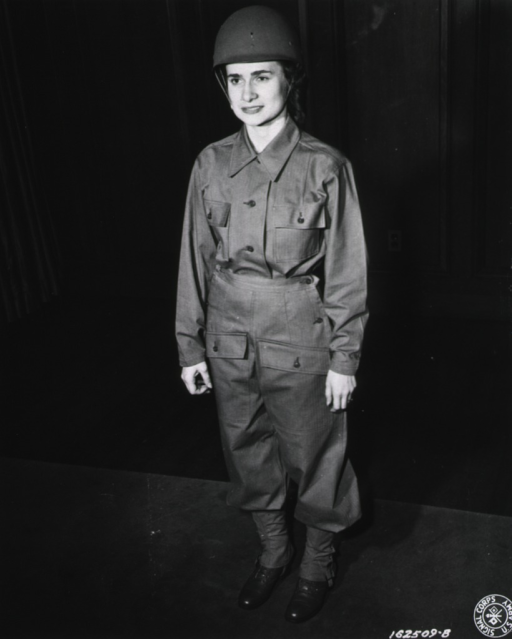 <p>A servicewoman stands on a carpet and poses full-face as she models the uniform.</p>